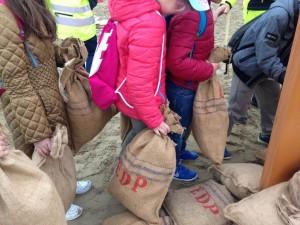 Al lavoro, in collaborazione, per sistemare i sacchi di sabbia anti-allagamento!